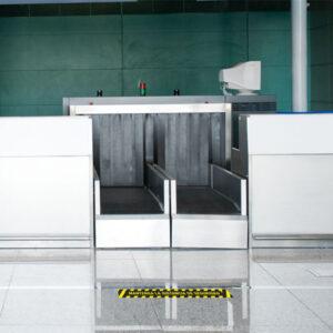 Vinilo adhesivos de suelo, mantenga la distancia de seguridad, rayas amarillo y negro, en el suelo de un aeropuerto