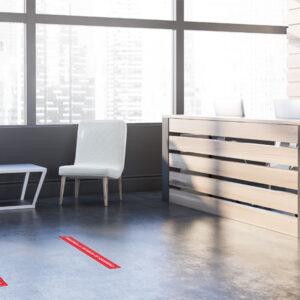 Muestra de vinilos adhesivos, mantenga la distancia de seguridad, en el suelo de una oficina